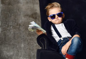 Happy and shoutting rich kid boy millionaire sits with a bundle of money dollars cash in big luxury armchair while bills falling